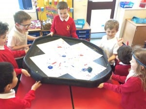 The children tried rolling a ball through paint to create patterns.